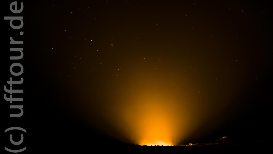 Aus ein paar hundert Metern Entfernung bietet sich ein tolles Bild vor dem Sternenhimmel (zum Größenvergleich: Das kleine helle Viereck rechts neben dem Feuerschein ist unser LKW).