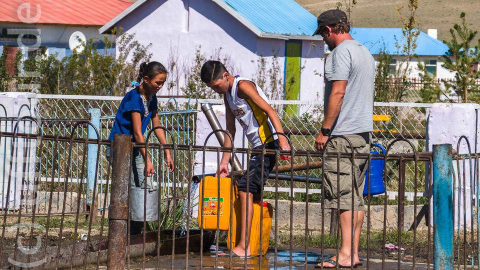 Öffentliche Wasserstelle mitten im Dorf. Alle holen hier ihr Wasser. Sebastian wartet mit seiner Gießkanne geduldig.